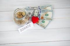 Donationer och välgörenhet Donationbegrepp Exponeringsglas med donationer på vit bakgrund Inskriften donerar Välgörenhet och peng fotografering för bildbyråer