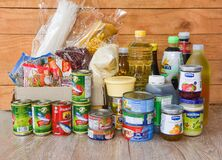 Donations box with canned food on wooden table background / pasta canned goods and dry food non perishable with oil rice noodles