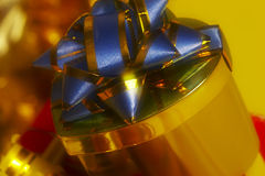 Donative. Golden gift with blue bow Stock Image