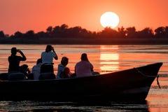 Donaudelta, Rumänien, Augusti 2017: turister som håller ögonen på solnedgången royaltyfri foto