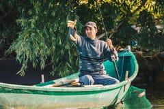 Donaudelta, Rumänien, Maj 2018: Fiskare som fångar fisken i hans royaltyfri fotografi