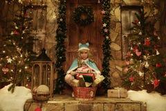 Doncella de la nieve con los presentes en el umbral de la casa adornado en estilo de la Navidad Imágenes de archivo libres de regalías