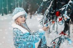 Doncella de la nieve retrato de una niña en invierno en traje festivo elegante el niño adorna el árbol de navidad en el bosque imagen de archivo