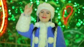 Doncella sonriente de la nieve que agita su mano en el árbol de navidad almacen de metraje de vídeo