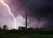 Donder, bliksem en onweer over verlaten fabriek in de zomer Stock Foto's