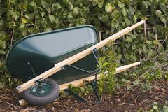 Done. A wheelbarrow lies on its side in the ivy Royalty Free Stock Image