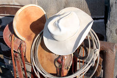 Done for the day. Cowboy hat with saddle and rope Stock Images