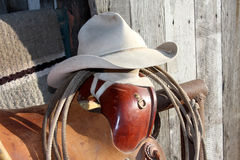 Done for the day. Cowboy hat with saddle and rope royalty free stock photo