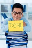 Done!. Happy young Asian businessman with all his paperwork done royalty free stock photography