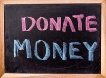 Done la palabra del dinero en la pizarra Fotos de archivo