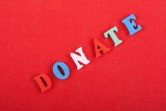 DONE la palabra en el fondo rojo compuesto de letras de madera del ABC del bloque colorido del alfabeto, copie el espacio para el Foto de archivo libre de regalías
