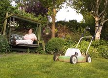 Done Mowing the Lawn. Humorous picture of a man who is proud of having mowing the lawn and is now sitting lazily in the garden, pulling a funny face Stock Image