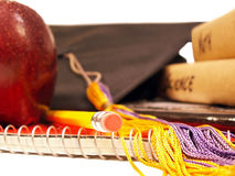 Done with school. Pile of books, pencil, apple and graduation cap with tassel stock photos