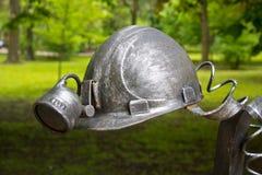 Donec'k, Ucraina - 9 maggio 2017: Il casco del ` s del minatore ha forgiato le figure forgiate da metallo Fotografia Stock