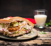 Doner kebab用肉、调味汁和菜与玻璃airan在一块板材在木土气背景,关闭 库存照片