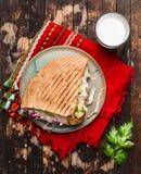 Doner kebab用肉炸肉排和菜在一块板材有一块红色餐巾的和蒜酱油在木土气背景,顶视图 库存图片