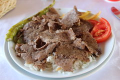 Doner Kebab. Famous dishes of Turkish doner kebab . service was put on rice, next to tomatoes, peppers, imposed fries Stock Images