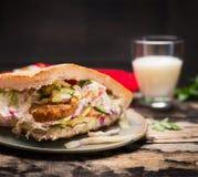 Doner-Kebab mit Fleisch, Soße und Gemüse mit einem Glas-airan auf einer Platte auf hölzernem rustikalem Hintergrund, Abschluss ob Stockfotos
