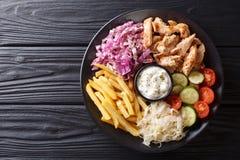 Doner kebab na talerzu z dłoniakami, sałatką i kumberlandem w górę stołu francuza, dalej horyzontalny odgórny widok obraz stock