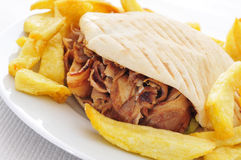 Doner kebab. A doner kebab in a plate with french fries on a set table Royalty Free Stock Photo