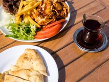 Doner kebab on the plate with french fries, tomatoes, onion and salad. Grilled chicken and lamb meat with vegetables and pita royalty free stock photos
