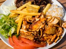 Doner kebab on the plate with french fries, tomatoes, rice, onion and salad. Grilled chicken and lamb meat with vegetables.
