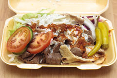 A doner kebab in styrofoam container. A doner kebab with chillies, salad, tomatoes, cucumber and chilli sauce in a styrofoam container Stock Photography