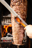 Doner meat being sliced from rotating spit Stock Photo