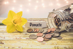 Donera begreppet för besparingar för besparingpengarkruset det motivational arkivbilder