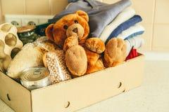 Donera begreppet - mat, kläder, leksaker i papp royaltyfri fotografi