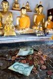 Donerade pengar under statyn av Buddha Arkivbild