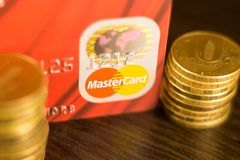 DONETSK, УКРАИНА 2-ое ноября 2017: Красная основная перфокарта среди куч золотых монеток Стоковое Изображение