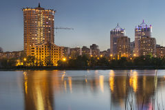 Donetsk City downtown skyline at dusk with skyscrapers illuminat. Ed over Kalmius river. Modern skyscrapers, building construction, lights and reflections at royalty free stock images
