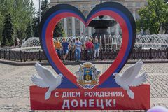 Donetsk, Ucrânia - 26 de agosto de 2017: Crianças na fonte e o simbolismo do estado autoproclamado no quadrado central fotografia de stock royalty free