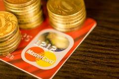DONETSK, UCRAINA 2 novembre 2017: Master Card rosso fra i mucchi delle monete dorate Fotografia Stock