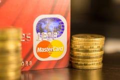 DONETSK, UCRAINA 2 novembre 2017: Master Card rosso fra i mucchi delle monete dorate Fotografie Stock