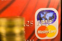 DONETSK, UCRANIA 2 de noviembre de 2017: Master Card rojo entre las pilas de monedas de oro Foto de archivo