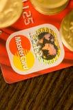 DONETSK, UCRANIA 2 de noviembre de 2017: Master Card rojo entre las pilas de monedas de oro Fotos de archivo libres de regalías