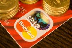 DONETSK, UCRANIA 2 de noviembre de 2017: Master Card rojo entre las pilas de monedas de oro Fotografía de archivo