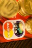 DONETSK, UCRANIA 2 de noviembre de 2017: Master Card rojo entre las pilas de monedas de oro Foto de archivo libre de regalías
