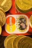 DONETSK, UCRANIA 2 de noviembre de 2017: Master Card rojo entre las pilas de monedas de oro Imagen de archivo libre de regalías