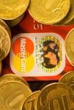 DONETSK, UCRANIA 2 de noviembre de 2017: Master Card rojo entre las pilas de monedas de oro Fotografía de archivo libre de regalías