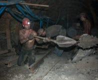 Donetsk Ukraina - Augusti, 16, 2013: Gruvarbetare utför den tunga handboken Arkivbild