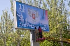 Donetsk Ukraina, Kwiecień, - 29, 2017: Pracownika kleidła sztandar w trakcie narządzania dla świętowania dzień Donetsk Peopl Obraz Stock