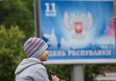 Donetsk Ukraina, Maj, - 09, 2017: Chłopiec dzwoni dla świętowania na tle sztandar Zdjęcia Royalty Free