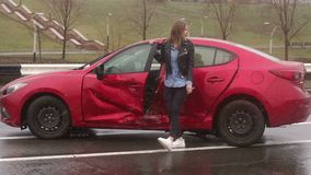Donetsk, Ukraine - April 5, 2019: Portrait of a emotional girl who got into a car accident on the road in the rain stock video footage