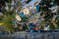 Donetsk, Ukraine - August 27, 2017: Townspeople riding amusement rides in the Shcherbakov park Stock Photos