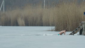 DONETSK, UKRAINE-JANUARY 19: Boy swimming in a ice-hole. Orthodox tradition stock video footage