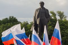 Donetsk, Ukraine - June 12, 2019: Flags of Russia and the monument to Vladimir Lenin on the central square. During the celebration of the Day of Russia stock photography