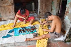 Dong Anh, Hanoi, Vietnam - 20 de septiembre de 2015: Un hombre y su esposa hacen la madera que tallan productos delante de su cas Imagen de archivo